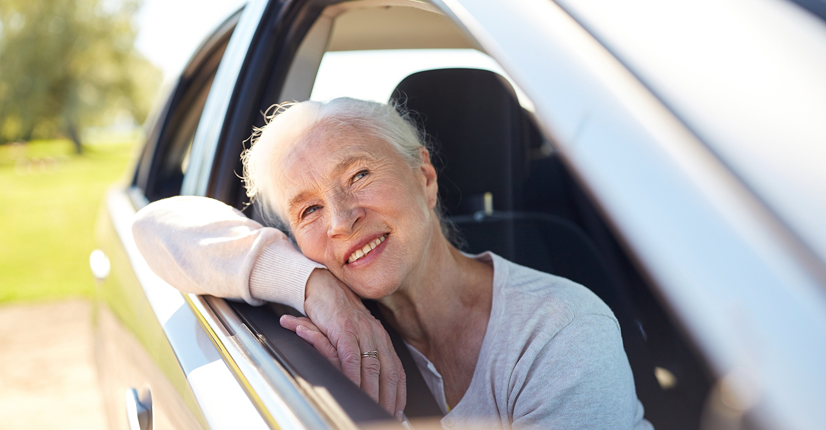 happy senior woman driving in car with open window