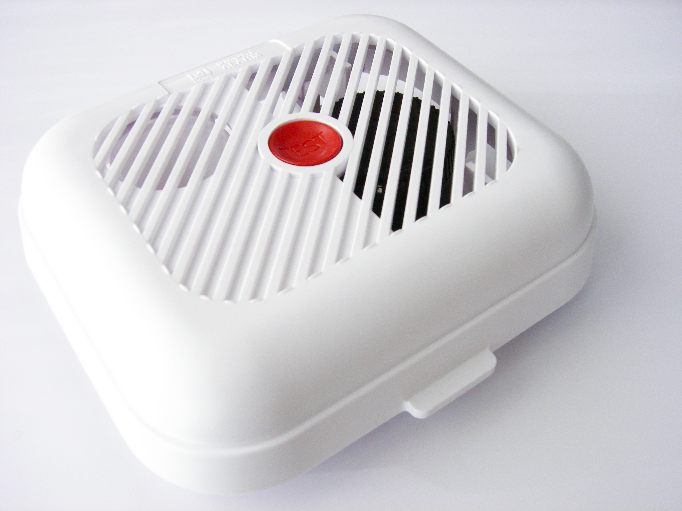 White smoke alarm with red button